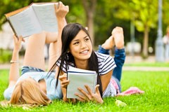 picture of a young girls lying on the grass reading